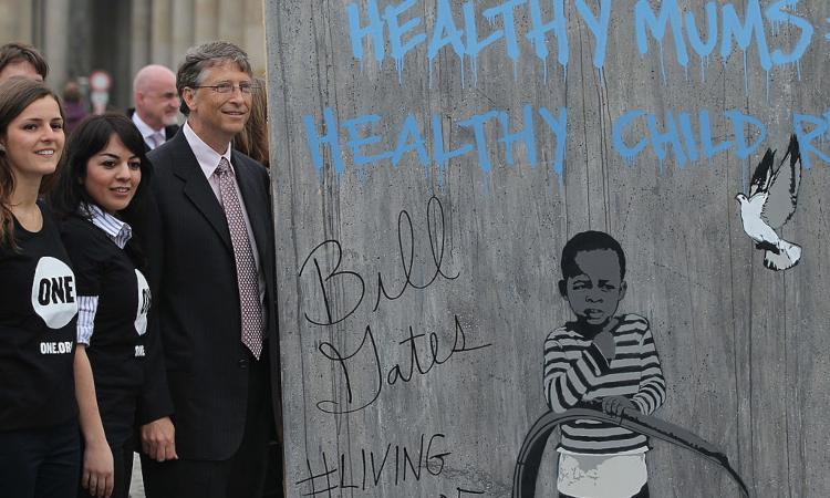 Bill Gates posa vicino a un murales