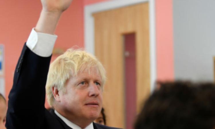 Il premier inglese, Johnson, alza la mano in classe