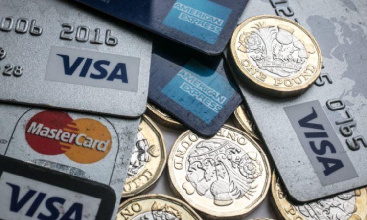 Alcune monete e due tipi di carte di credito