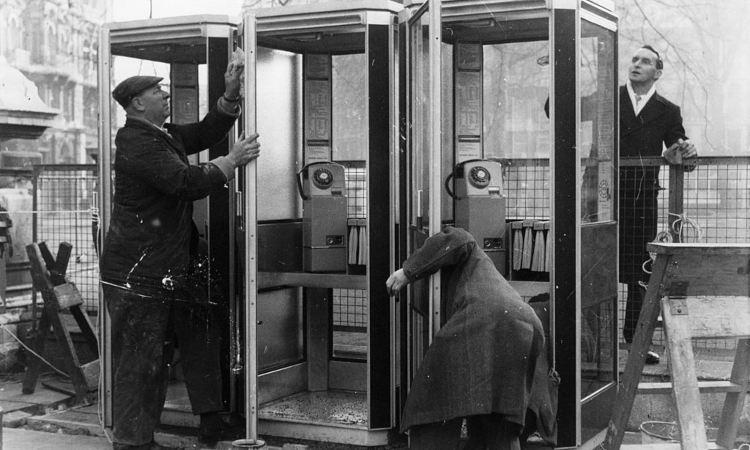 Tre uomini aggiustano le cabine telefoniche