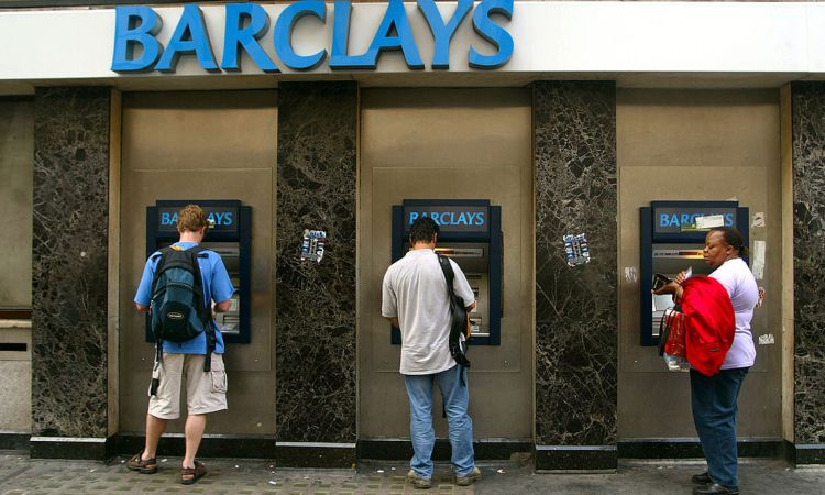 Tre uomini sono allo sportello automatico di una banca