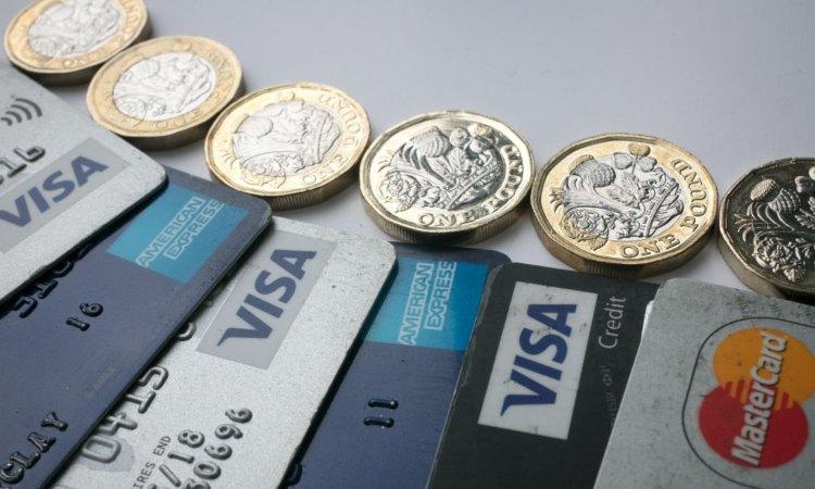 Alcune monete reali vicino a delle carte di pagamento digitale