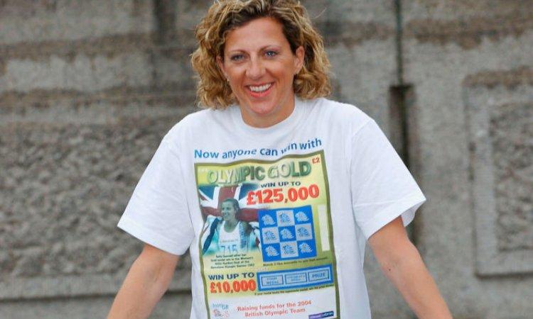Una donna sorridente mostra la t-shirt di un gratta e vinci
