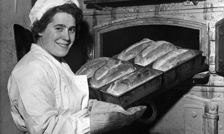 Una signora con una teglia di pane fra le mani