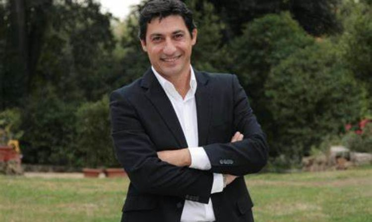 Emilio Solfrizzi sorride con le mani incrociate