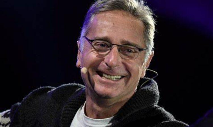 Paolo Bonolis sorride con un microfono