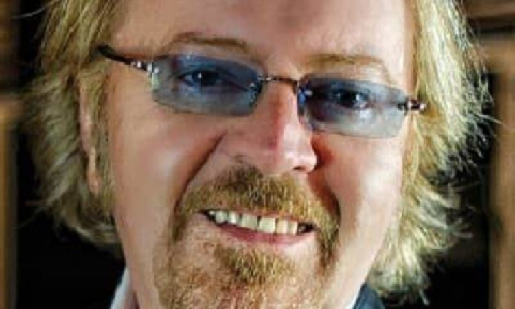 Umberto tozzi sorride con gli occhiali blu
