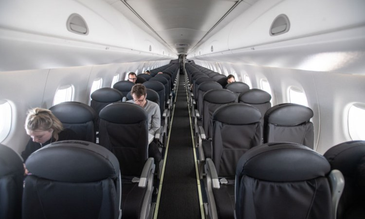 Alcuni passeggeri seduti sui sedili di un aereo