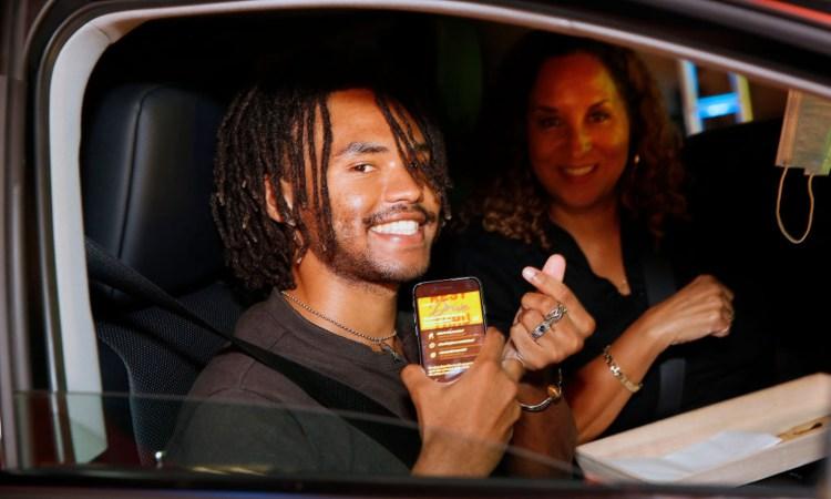 Un ragazzo sorridente fa il gesto dei soldi con le dita