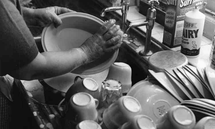 Persona che pulisce piatti e bicchieri a casa