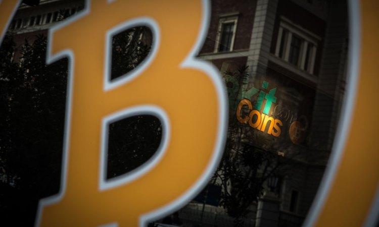 Il simbolo giallo di BTC con la scritta coins sullo sfondo