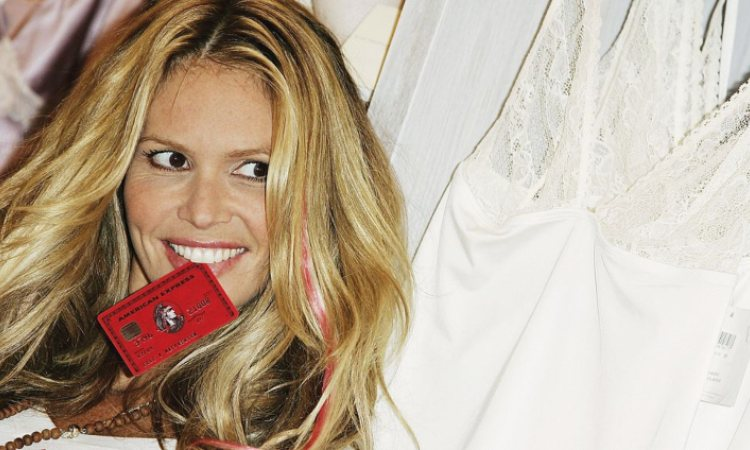 Una modella posa con una carta di credito in bocca