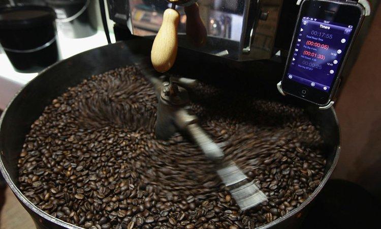 Un tellefono cellulare vicino a dei chicchi di caffè