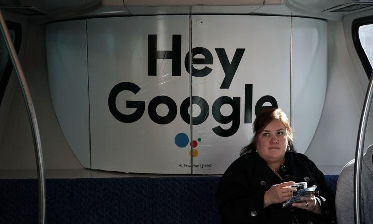 "Una donna seduta vicino la scritta ""Hey Google"""