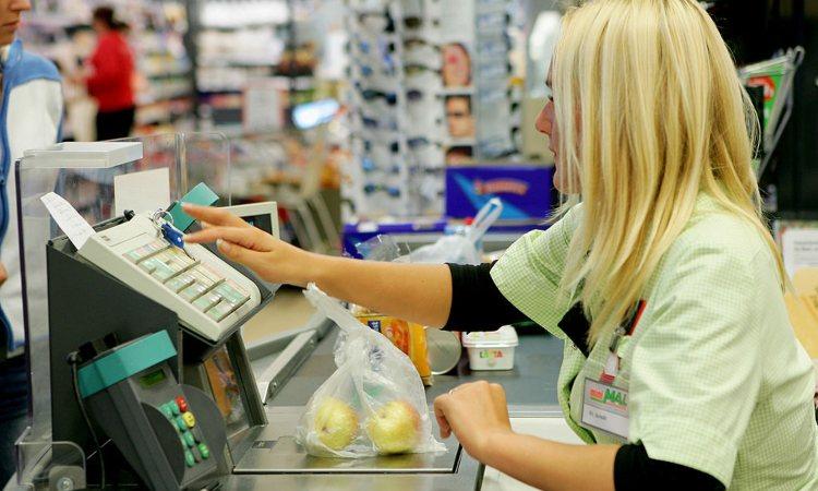 La cassiera di un negozio fa pagare dei prodotti
