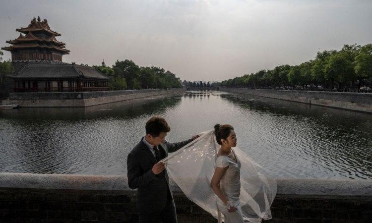Due sposini si lasciano fotografare sulle rive di un fiume