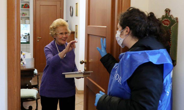 Una signora anziana sulla porta di casa