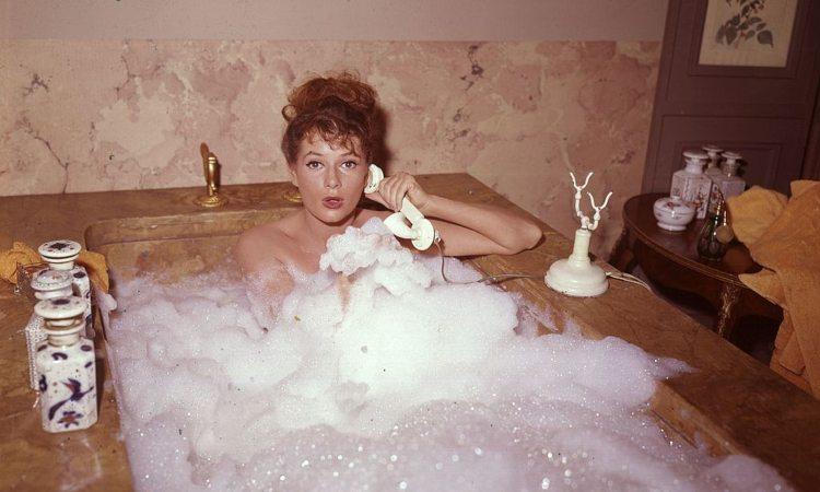 Una donna parla al telefono dentro una vasca da bagno piena di schiume