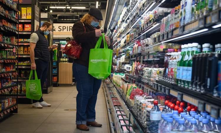 Una persona con uno smartphone in mano mentre fa la spesa