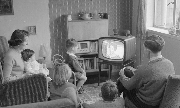 Un po' di persone di fronte a una tv