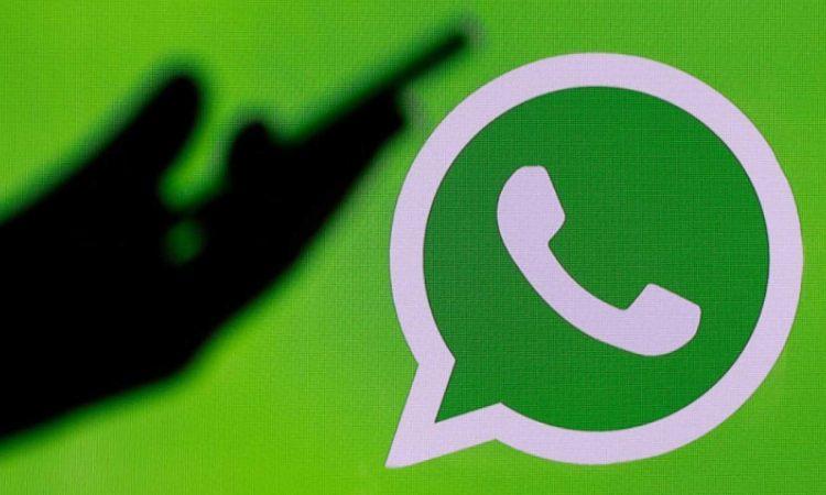 Il logo di Whatsapp e una mano in penombra