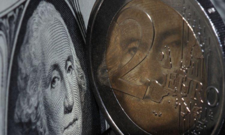 Una moneta da 2 euro vicino ad una banconota dei dollari