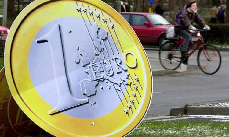 Una moneta da un euro in primo piano e una bicicletta sullo sfondo