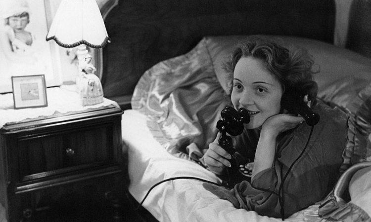 Una donna mentre parla al telefono in camera da letto