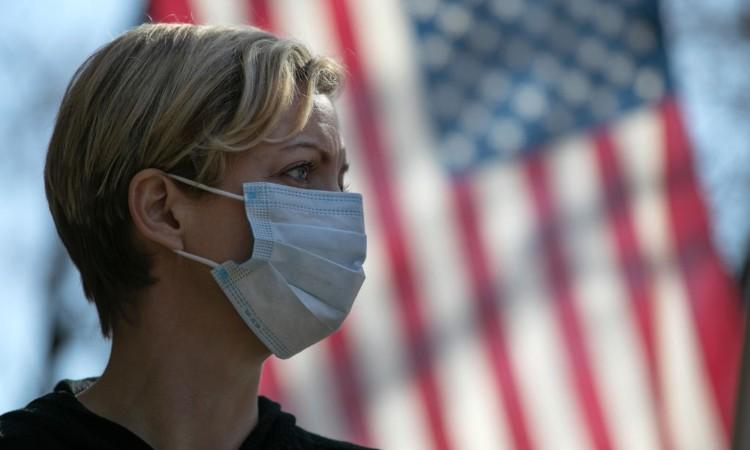 Una ragazza con la mascherina e una bandiera degli Usa