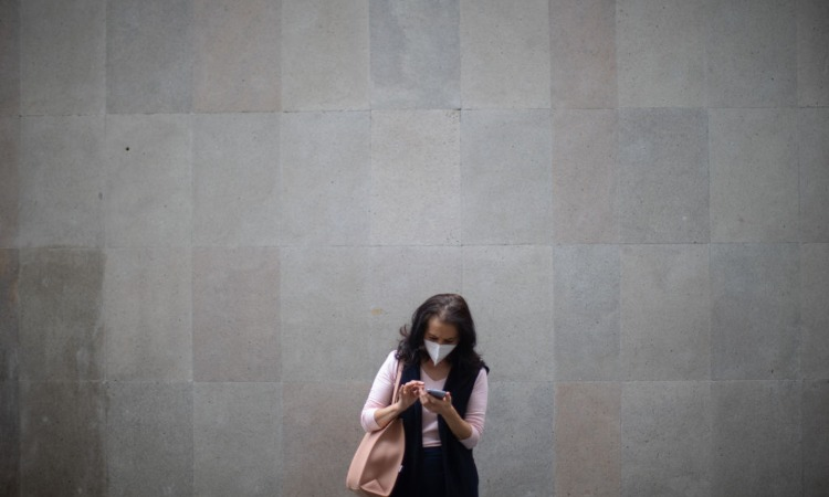 Una donna intenta a guardare lo schermo di un cellulare