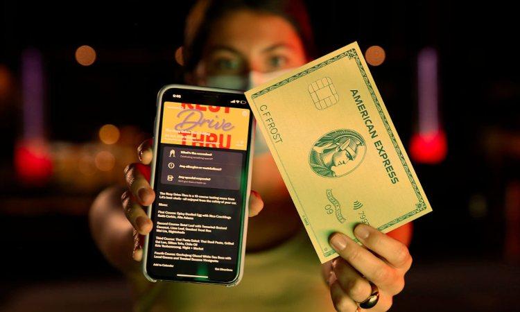 Una persona con in mano una finta carta di credito e uno smartphone