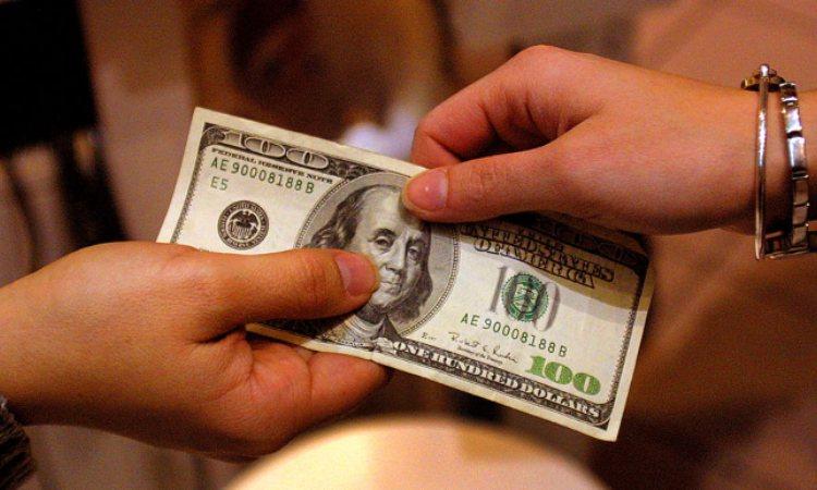Una mano passa una banconota ad un'altra