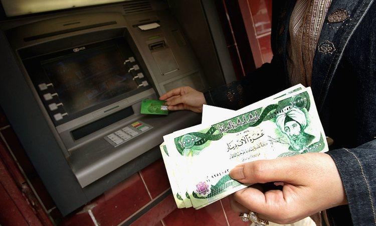 Una persona a uno sportello automatico con dei soldi in mano