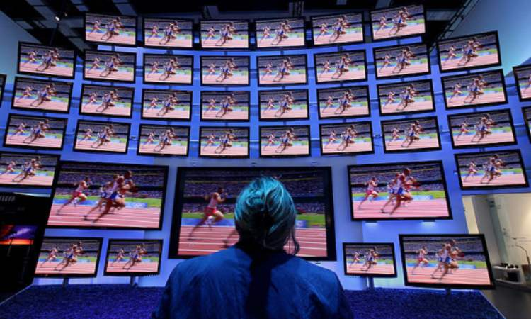 Una persona davanti ad alcuni schermi delle tv