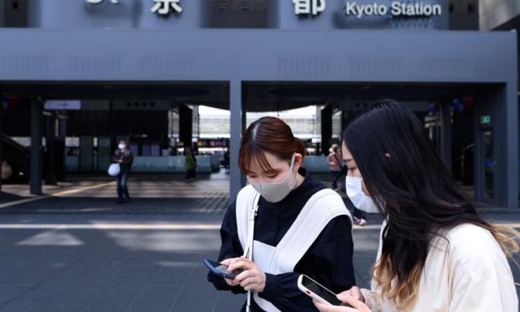Due ragazze con mascherina indossata e smartphone tra le mani