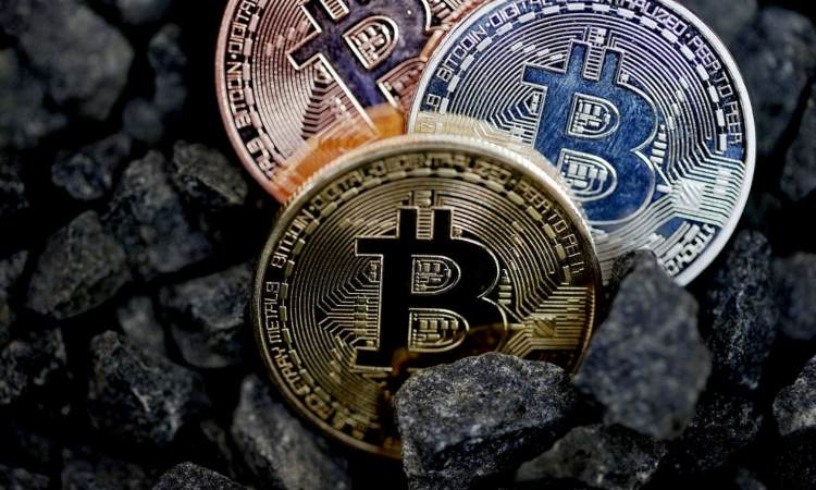 Tre monete dei BTC poggiate su dei sassi neri