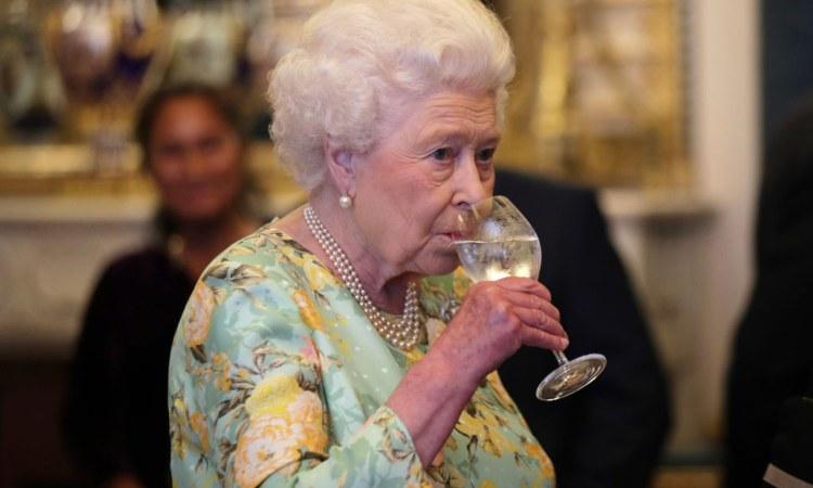 La regina Elisabetta con un bicchiere d'acqua in mano