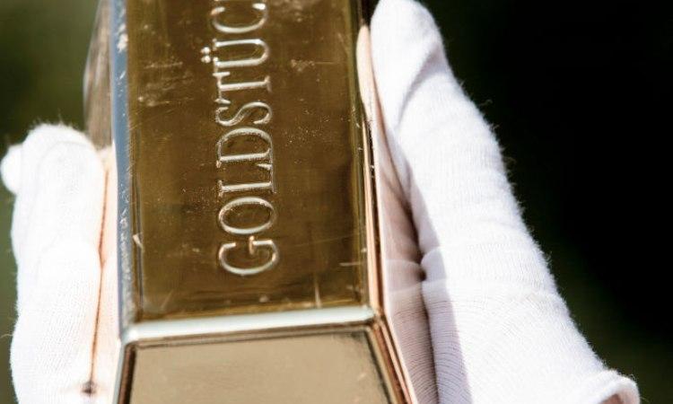Una mano con guanti tiene un lingotto d'oro