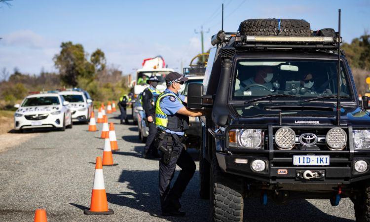 Alcuni agenti di polizia controllano dei cittadini nelle automobili
