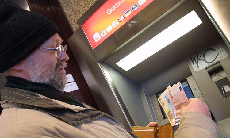 Un uomo mentre ritira delle banconote allo sportello automatico