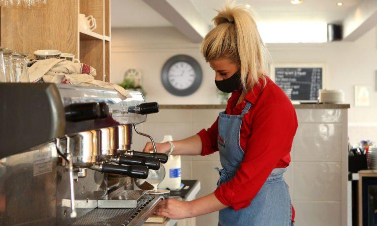 Una persona mentre fa un caffè alla macchinetta del bar
