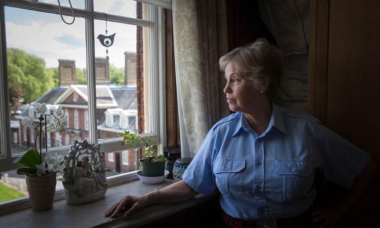 Una donna con capelli grigi affacciata alla finestra