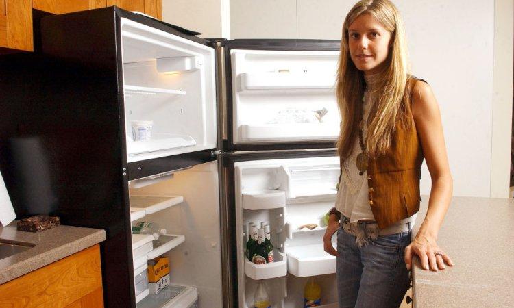 Una donna sorridente davanti a un frigorifero
