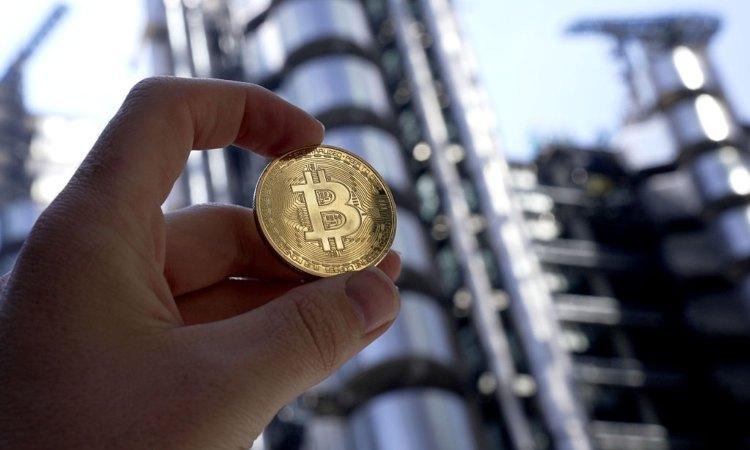 Una moneta dei bitcoin direzionata verso un palazzo