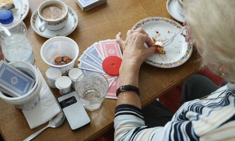 Una donna mentre mangia con il piatto sul tavolo