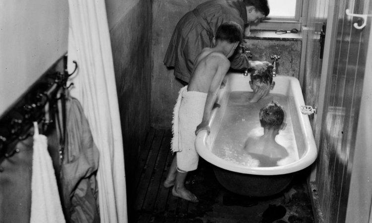 Dei bambini lavati dentro una vasca da bagno