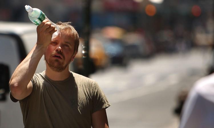 Un ragazzo con una bottiglia d'acqua sulla testa