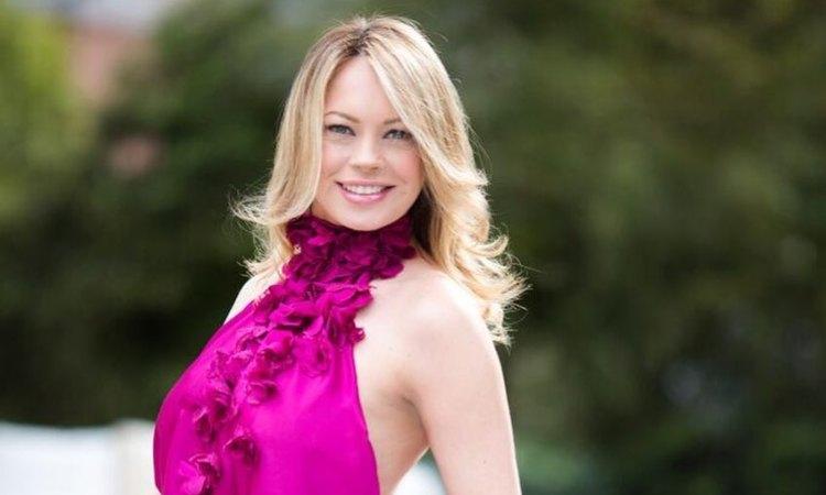 Anna Falchi sorride col vestito fucsia