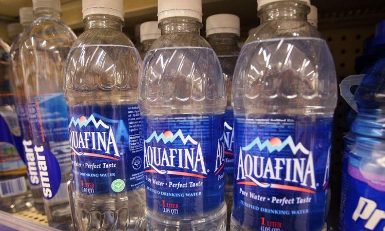 Un po' di bottiglie piccole d'acqua in vendita dentro un negozio