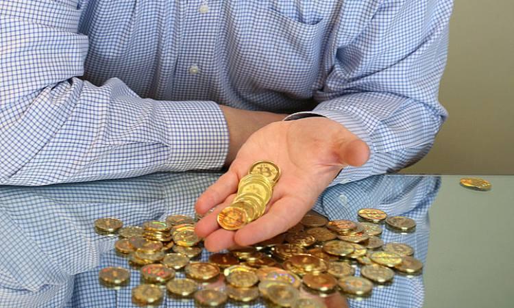 Una manciata di bitcoin dorate in moneta vicino a Mike Caldwell
